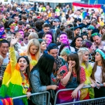 PRIDE festival in liverpool featuring people in a crowd in bright coloured clothing holding rainbow coloured flags.