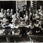 Black and White image of children and young people with military personnel celebrating VE day sitting at a long table with cake during a street party.
