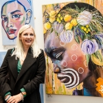 blonde lady wearing a black jacket and green shirt standing in front of a canvas taking up the whole background featuring an artistic piece of a head with yellow and green circles on it