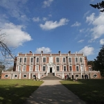 View of croxteth hall against the blue sky and white clouds with trees and gardens in front of the hall