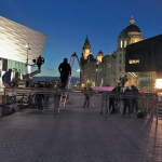 Liverpool waterfont in early evening, film crew filming outside of Liverpool Museum on the flat grey paving and the waterfront buildings are lit up in yellow against the night sky behind the film crew.