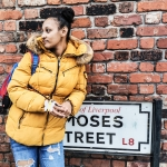 girl in a yellow puffer jacket and light blue ripped heans with a blue backpack stands leaning against a black and white street sign saying L8 and a red brick wall is behind her. Image is copyright to 20 Stories High
