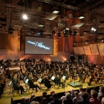 BBC Philharmonic perfoming indoors with red lighting