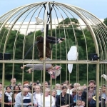 a giant birdcage with a person dressed as a mouse inside hanging upside down surrounded by people in a park watching for the liverpool without walls programme