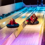 a lady and a young girl sliding down a slide with purple and blue lighting