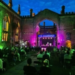 Liverpool Theatre Festival inside the grounds of bombed out church at night with green and purple uplights on the sides of the building and crowds sitting socially distanced on chairs