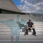 Artist on steps of Liverpool Museum next to a blue liver bird painted across each of the steps to his left
