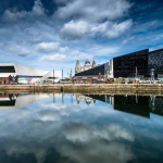 Liverpool docks and museum on the waterfront reflected in the dock against a blue sky with white clouds