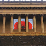 Front of st georges hall with the cenotaph in front of the building, and the three remembrance banners hanging from the columns