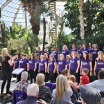 choir in purple t shirts in rows performing in front of a crowd inside the palm house in sefton park with lots of green trees and planting around them