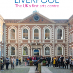 bluecoat front of the building with people in the courtyard during the day time