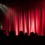 red curtains closed on a stage in a theatre with a spotlight on the stage from the left and the silhouettes of audience members for collective encounters