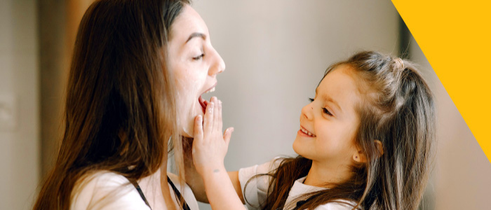 little girl playing with lady, placing her hands on her face