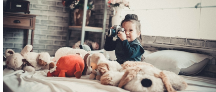 small child surrounded by soft toys playing with a camera