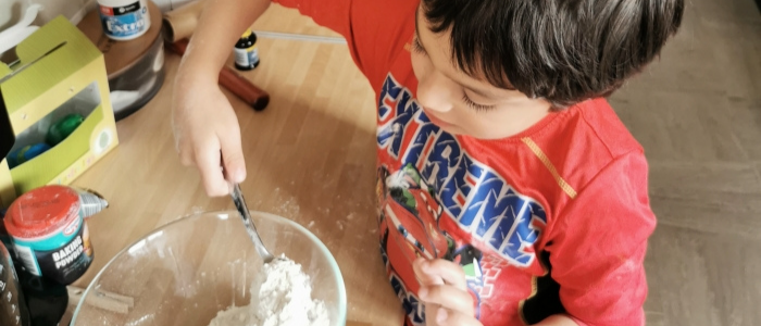 little boy in red t shirt mixing flour in a bowl