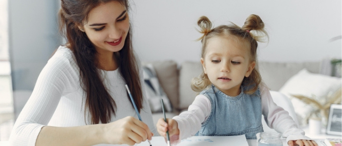 Little girl painting with adult next to her watching