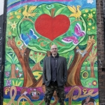 Ali Harwood in front of a wall murial