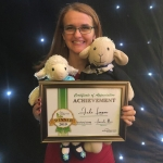 Jude Lennon holding up certificate and her stuffed toy lamb