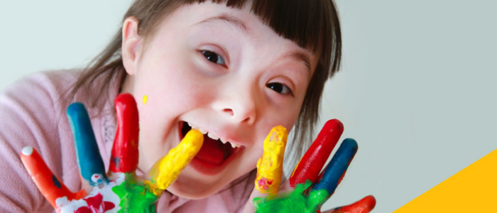 little girl with paint on her hands smiling