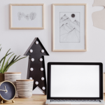 arrow on table pointing upwards, laptop open, clock on table and pot plants