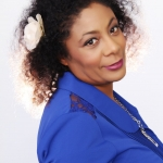 patrice lawrence in a blue jacket with a white flower in her hair