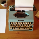 green typewriter on a brown table with white paper next to the left of typewriter