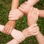 close up of peoples hands holding onto each others wrists in a circle