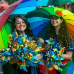 Two girls with long hair, one with face paint, under multi coloured rainbow umbrellas holding multicoloured giant flowers