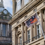flag hanging on flagpole on side of building with liverpool town hall dome in background for dot-art project