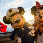 mickey mouse and minnie mouse on a boat with the disney flag in the background