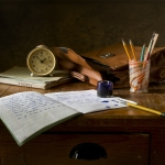 table with a n open notebook, pen pot with pens in a brown bag and a clock used for writing on the wall