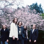 5 malaes standing in front of a pink blossom tree looking at camera for the music pilot