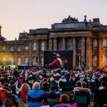 the greatest showman on a outdoor cinea screen at blenheim palace at dusk surrounded by crowds