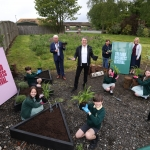 children sitting on the ground planting surrounded by good business festival branding on boards and metro mayor of liverpool