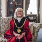 lord mayor mary rasmussen sittin gon a couch in mayoral robes in front of open curtains on a closed window