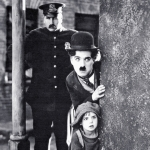 black and white photo of charlie chaplin peering round a wall corner with a small child, a police man stands in the background as part of the angel field festival