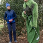 lady in green coat holding a golf stick in a forest next to a lady in a blue jacket and jeans a blue hat for national museums liverpool