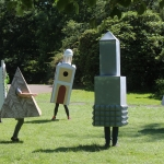 a parade of architectural commas performing in an outdoor park called flatland