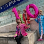 children dressed in beatles costume holding up a pink inflatable ten outside museum of liverpool