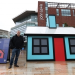 artist stood next to neon blue miniature bungalow called holiday home in Liverpool ONE