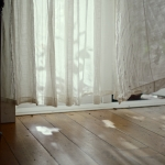 wooden floor with a net curtain blowing gently in the breeze