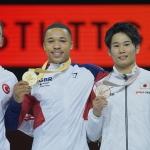 world gymnastic medal holders - three men in white gymnastics uniform holding their medals