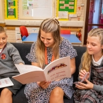 two school children enjoying reading a book with a blonde lady in the middle in their classroom