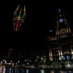 bbc spaceship projection on liverpool pier head at night with the liverpool liver building in the background